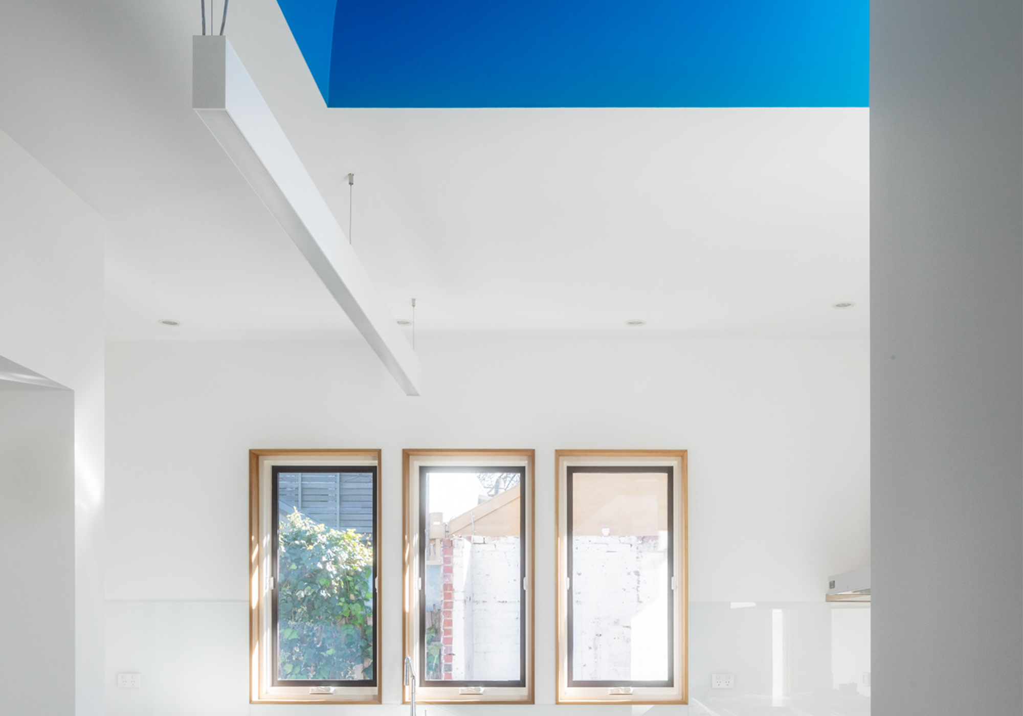 A tall narrow window above an existing boundary wall captures the morning light in Melbourne.